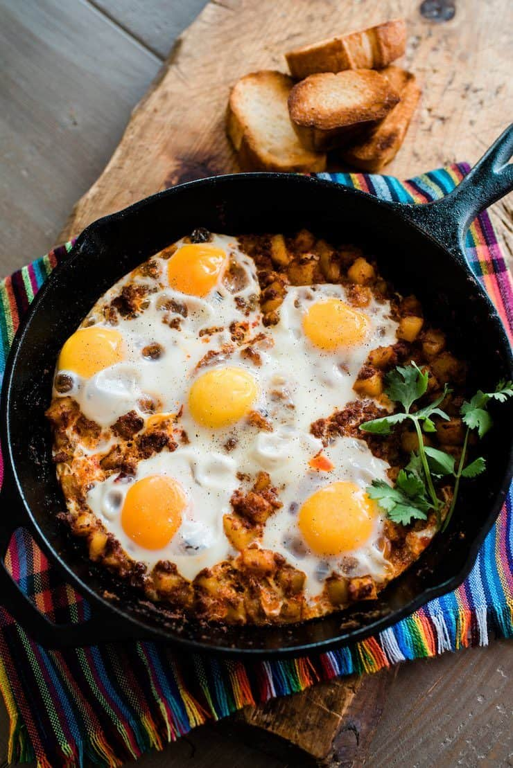Baked Eggs with Chorizo and Potatoes in an iron skillet on a colorful striped linen