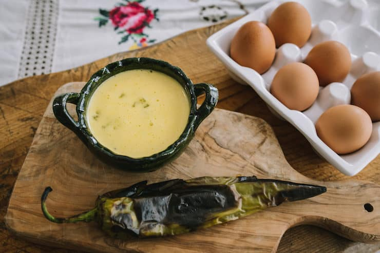 roasted green chile hollandaise sauce in a green bowl and eggs in a ceramic dish and roasted hatch Chile for eggs Benedict