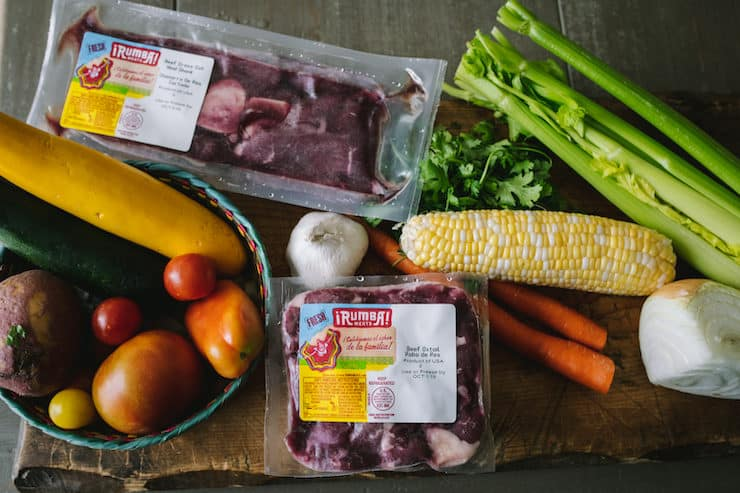 ingredients to make oxtail soup on a cutting board corn, celery, garlic, zucchini, tomatoes, beef, potatoes, carrots