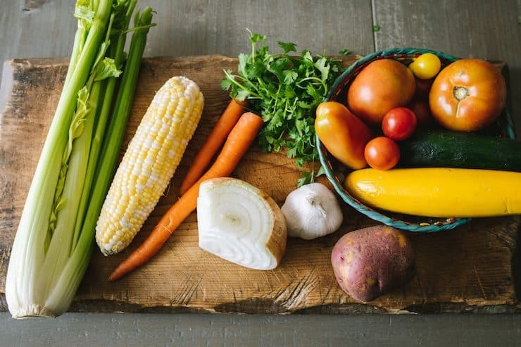 celery corn carrots garlic onion potato zucchini and tomatoes on an old wooden cutting board