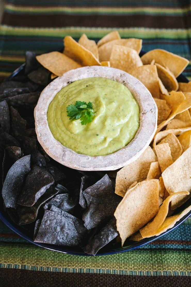 Avocado and Tomatillo Salsa in a white molcajete surrounded by tortilla chips
