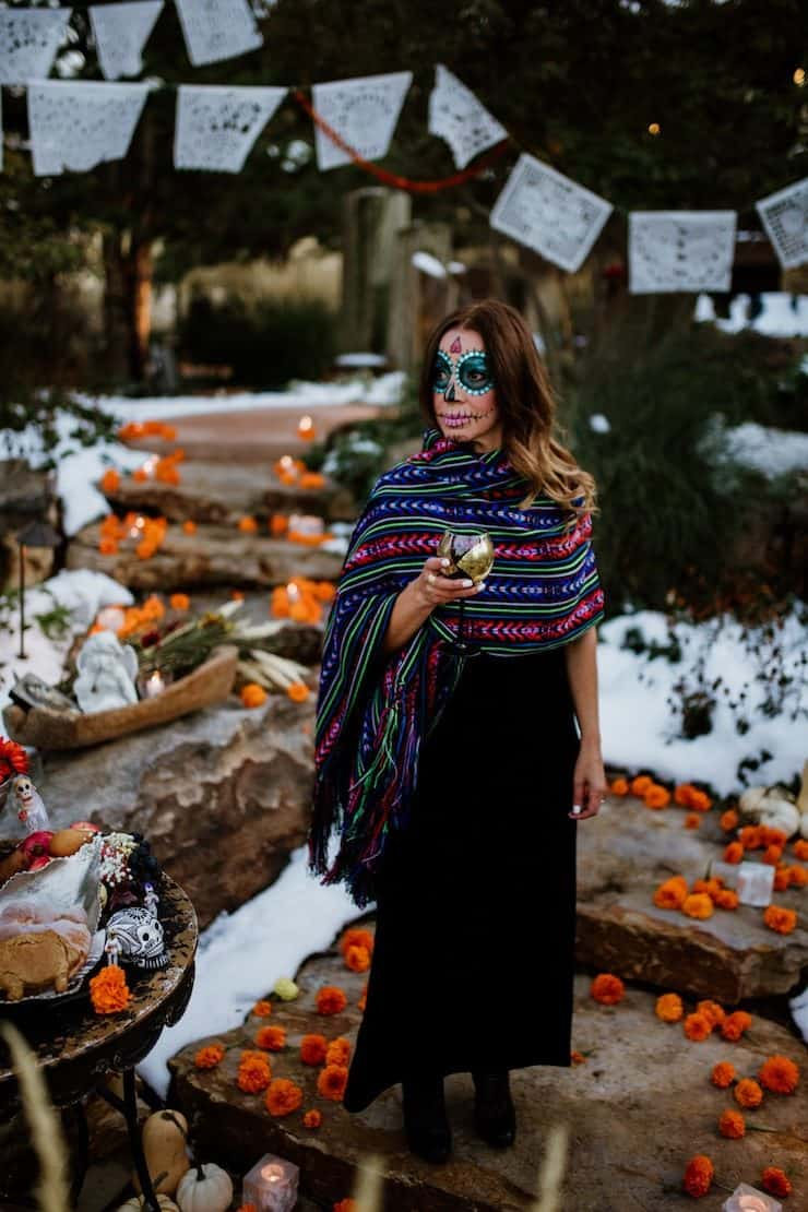 la Calavera Catrina holding wine glass papel picado in the background and marigolds