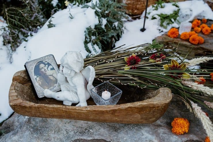 wooden bowl with a framed picture, a tea light candle, a small cherub statue, and marigolds to celebrate day of the dead