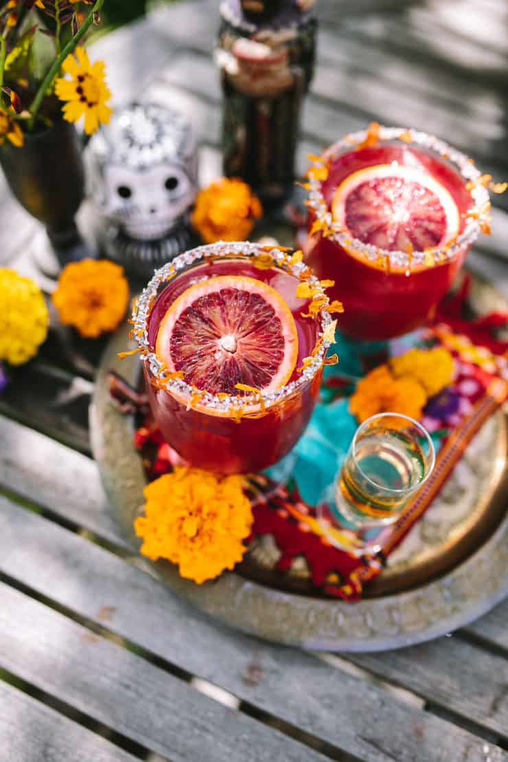 Day of the Dead setting two cocktails on a tray surrounded with marigolds and Blood Orange Marigold Margarita