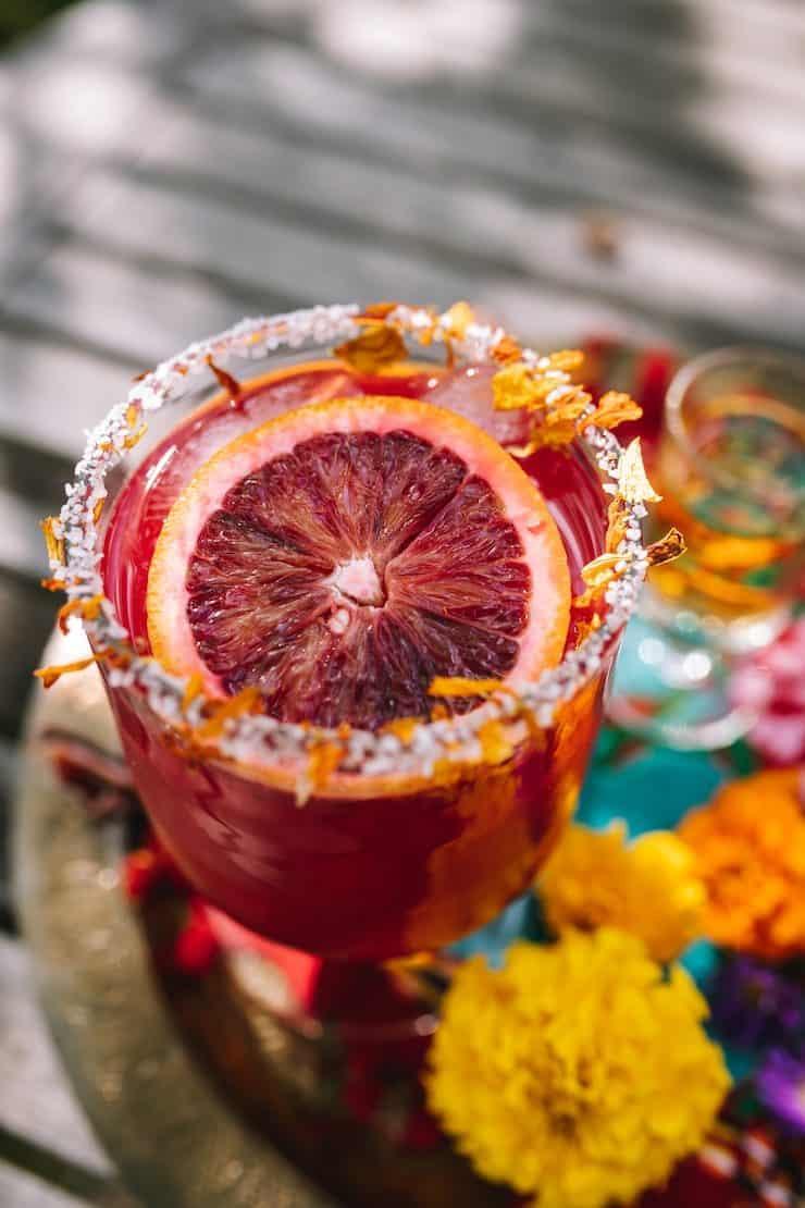 close up cocktail glass of a Blood Orange Marigold Margarita with a slice of blood orange