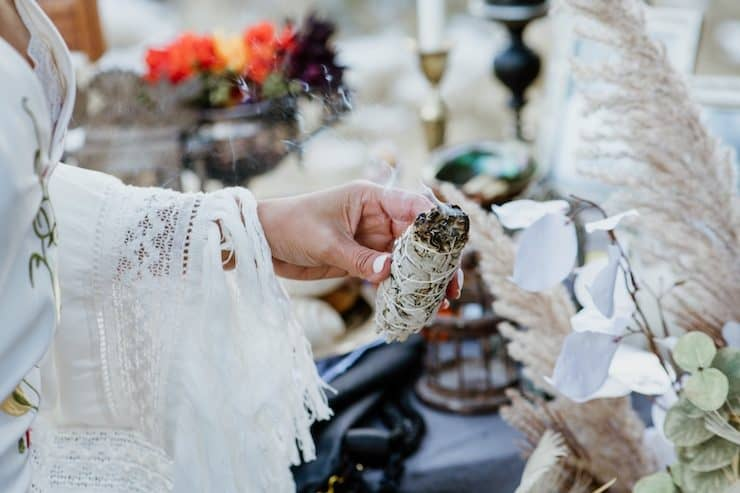 latina in a white dress holding a sage smudge stick for day of the dead celebrations