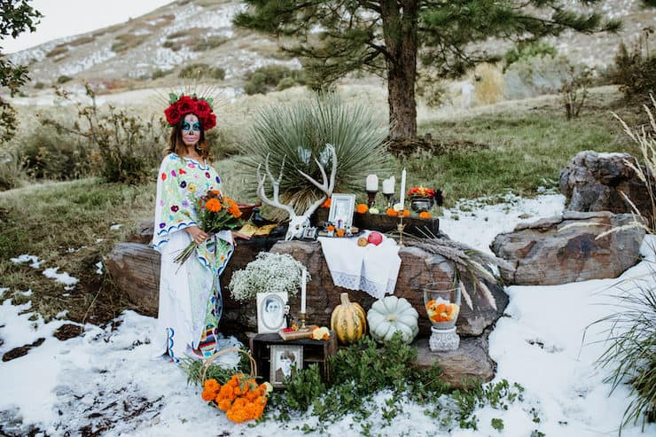 La Calavera Catrina in front of an altar ofrenda with snow on ground