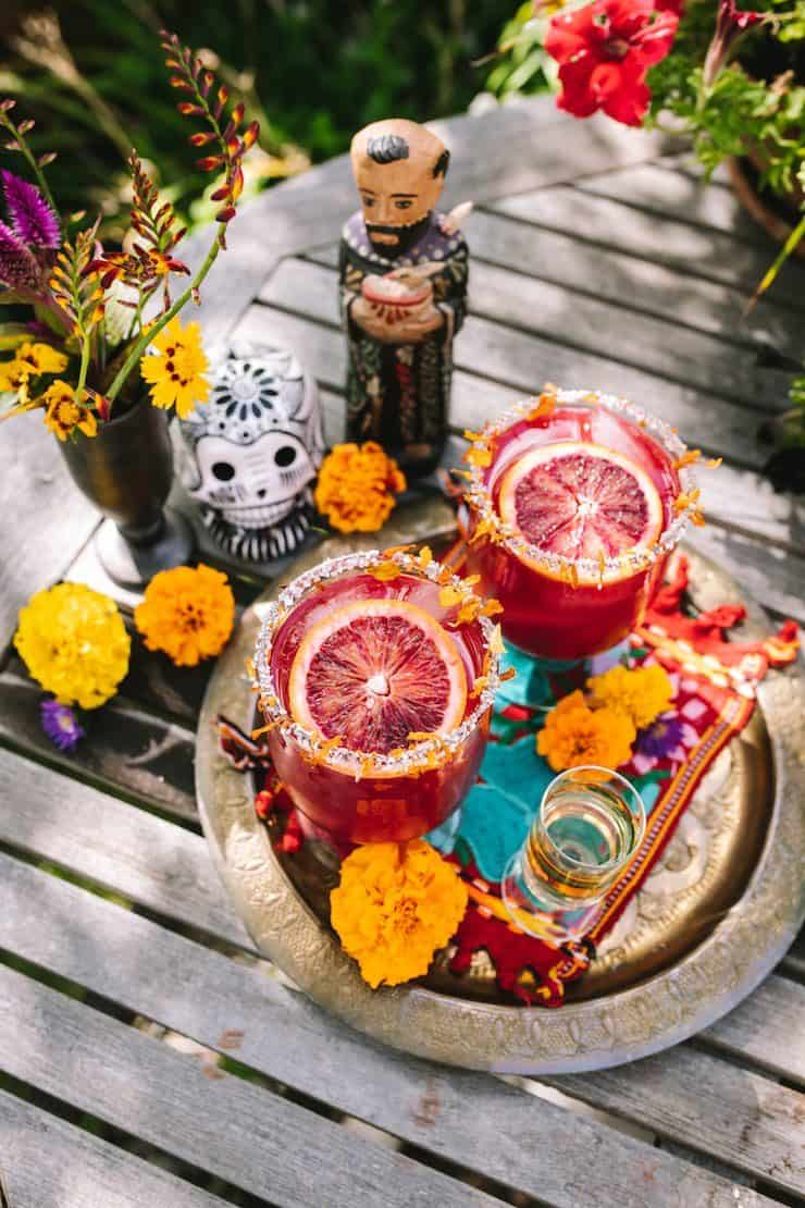st francis of assisi statue and sugar skull with tray with two blood orange margaritas