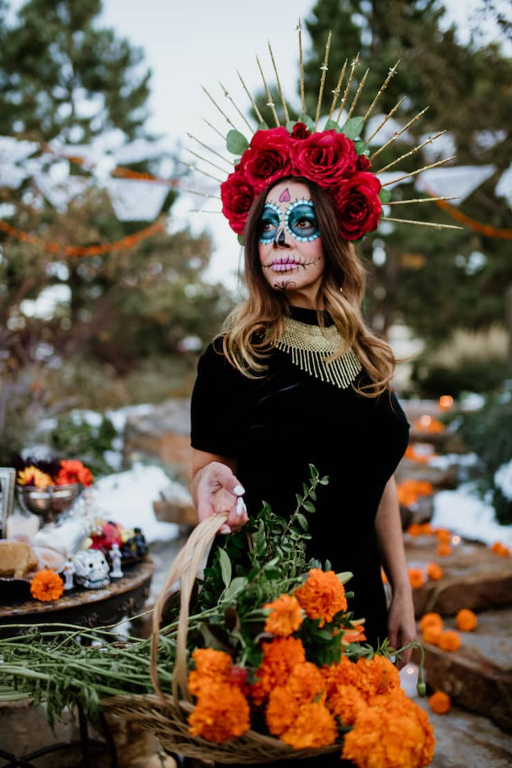 Calavera Catrina papel picado for day of dead lady wearing black dress and red rose crown holding basket filled with marigolds