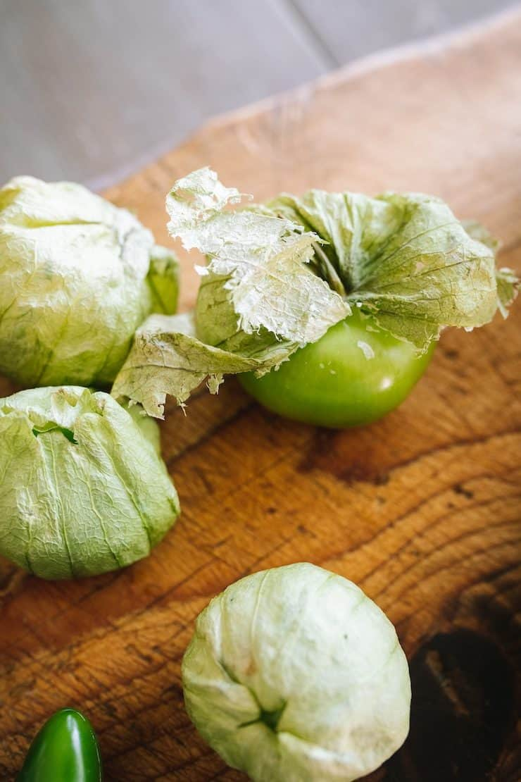 tomatillos on a cutting board to make Salsa de Guacamole or Guacamole Salsa