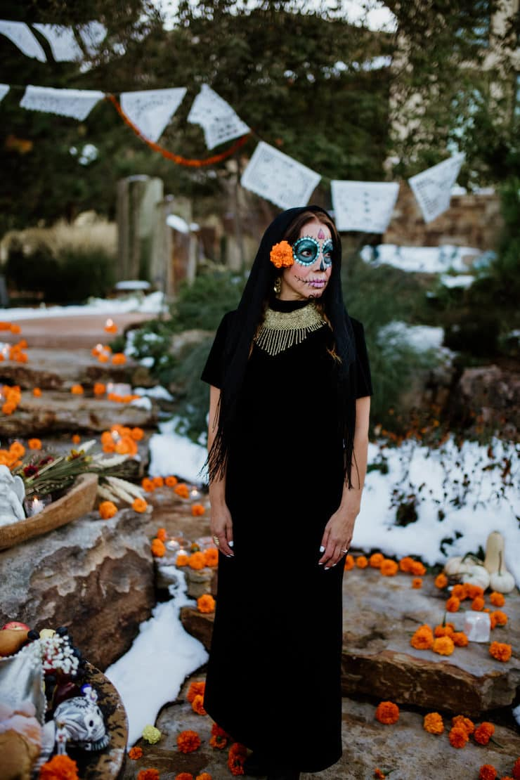 papel picado for Catrina day of dead lady wearing black on a path lined with marigolds