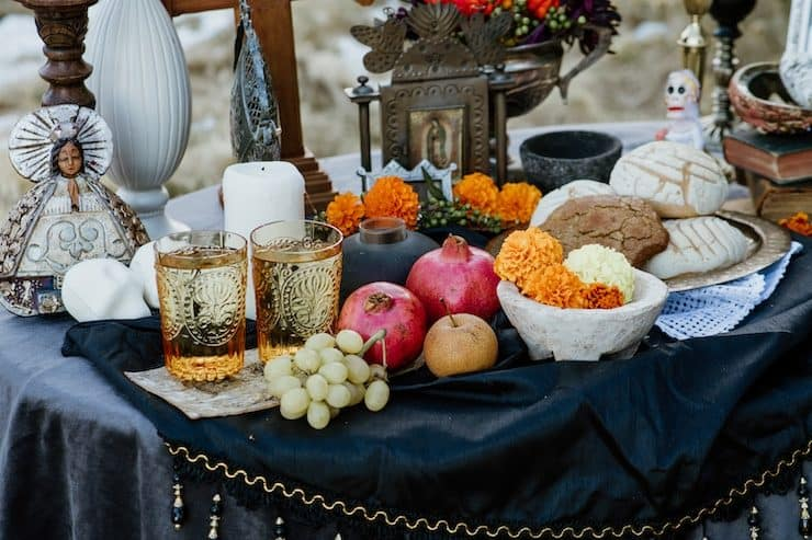 altar ofrenda elements water fruit flowers food photographs candles sugar skulls