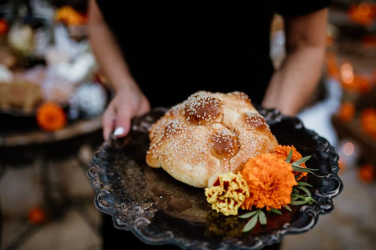 latina holding a black plate with two elements of dia de los muertos: special bread an marigolds for a day of the dead celebration