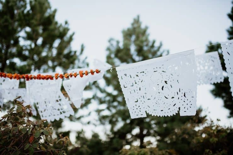 perforated decorated paper and marigolds strung up over a dia de muertos ofrenda