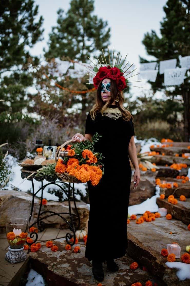 Calavera Catrina day of dead lady wearing black dress and red rose crown holding basket of marigolds