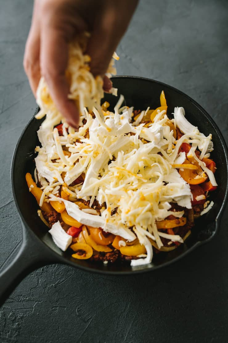 sprinkling Mexican cheese in a skillet to make Choriqueso (Queso Fundido with Chorizo)