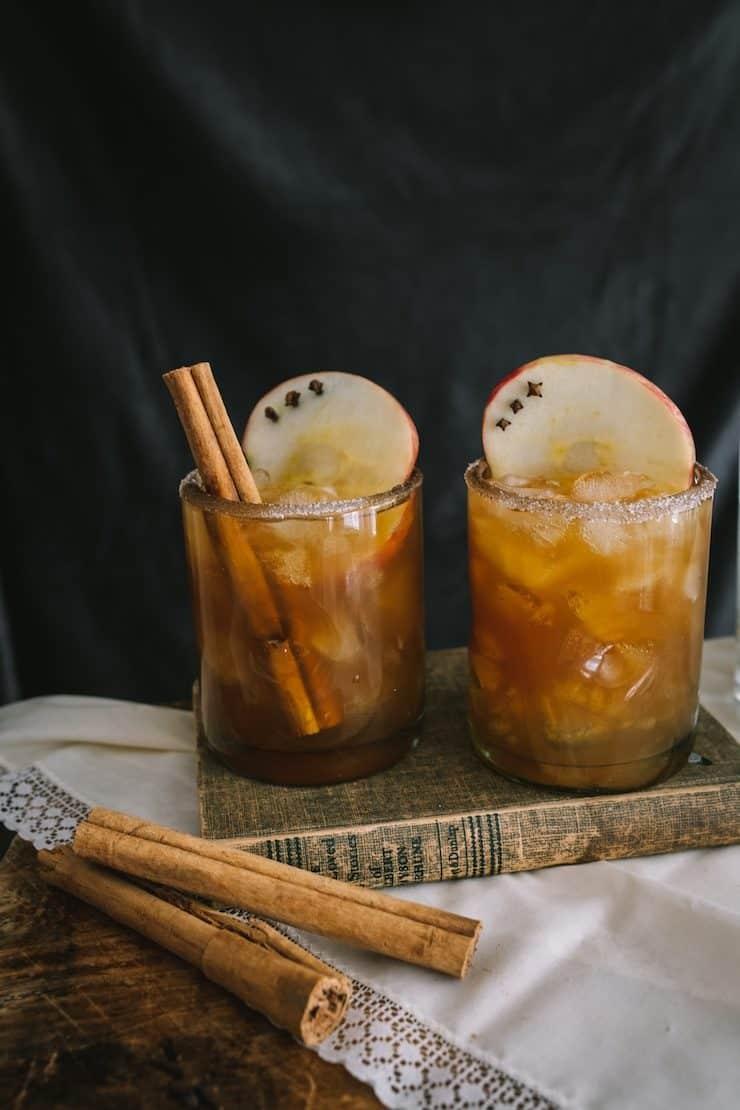 Manzana Paloma cocktails on a vintage book with cinnamon sticks