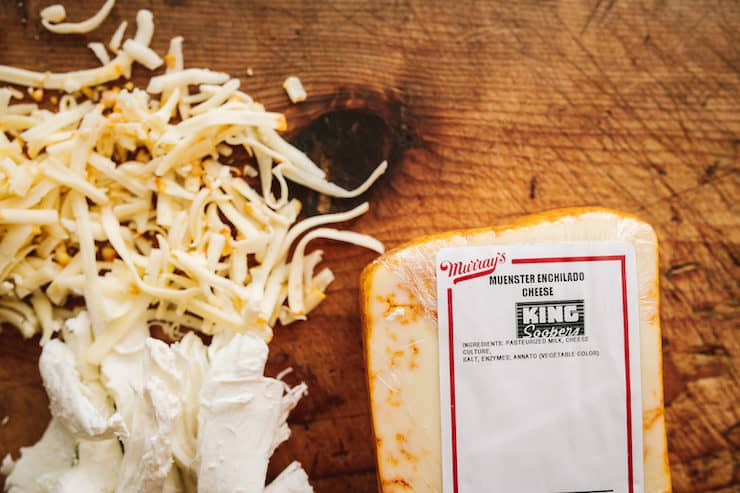 block of muenster cheese on a wooden cutting board next to shredded white cheese