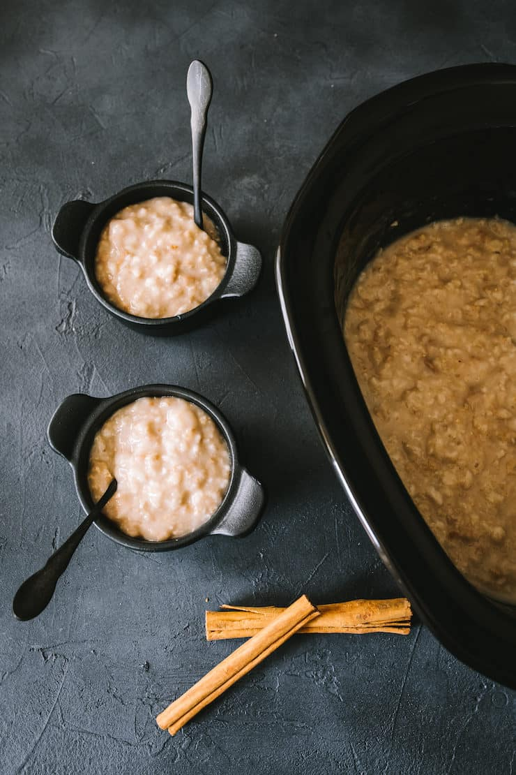 Slow Cooker Oatmeal and two black bowls of oatmeal and cinnamon sticks