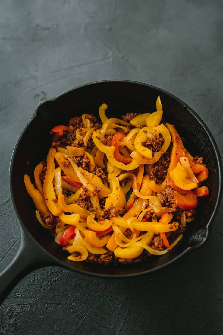 a skillet of sautéed bell peppers and onions for Choriqueso (Queso Fundido with Chorizo)