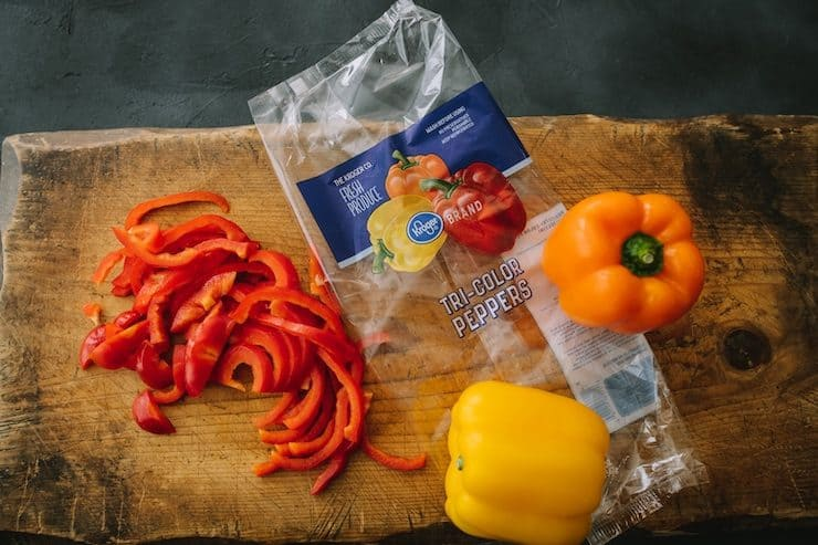 colorful bell peppers on a wooden cutting board for Choriqueso (Queso Fundido with Chorizo)