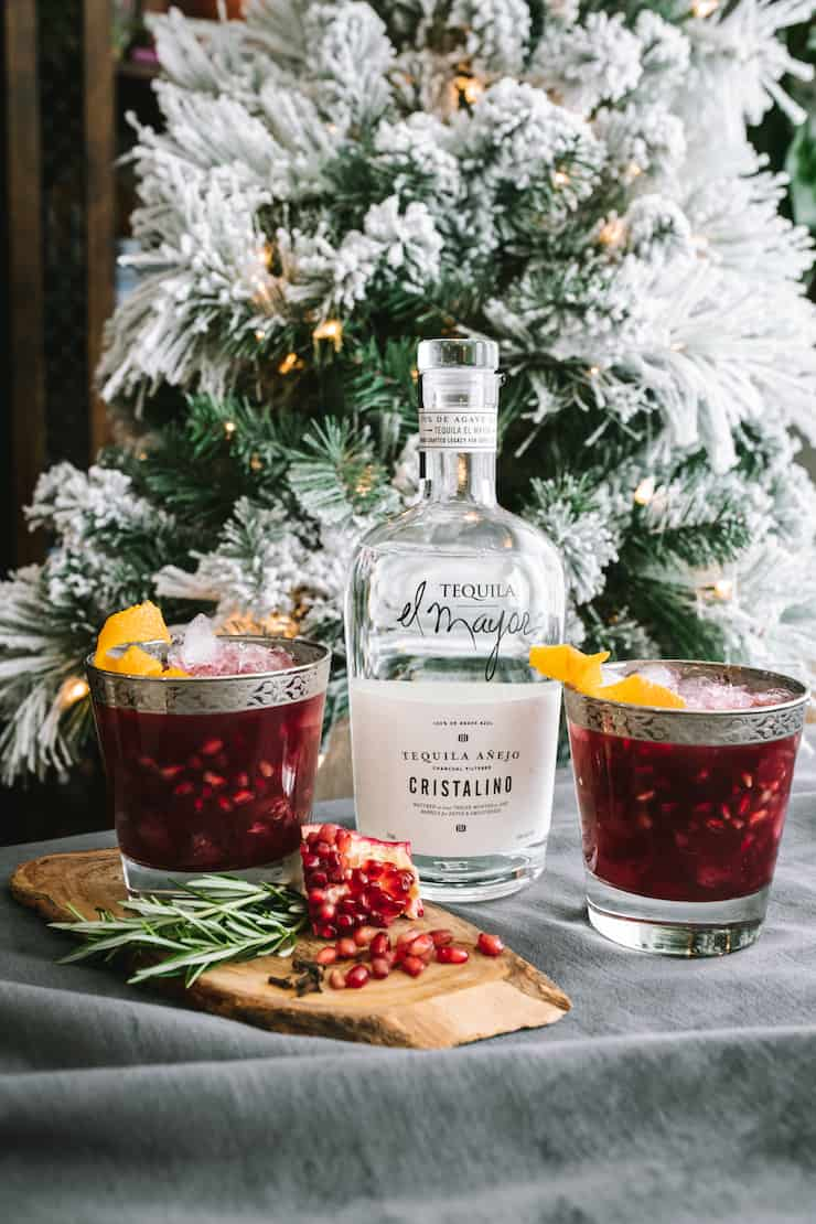 Pomegranate Margarita with tequila in front of Christmas tree
