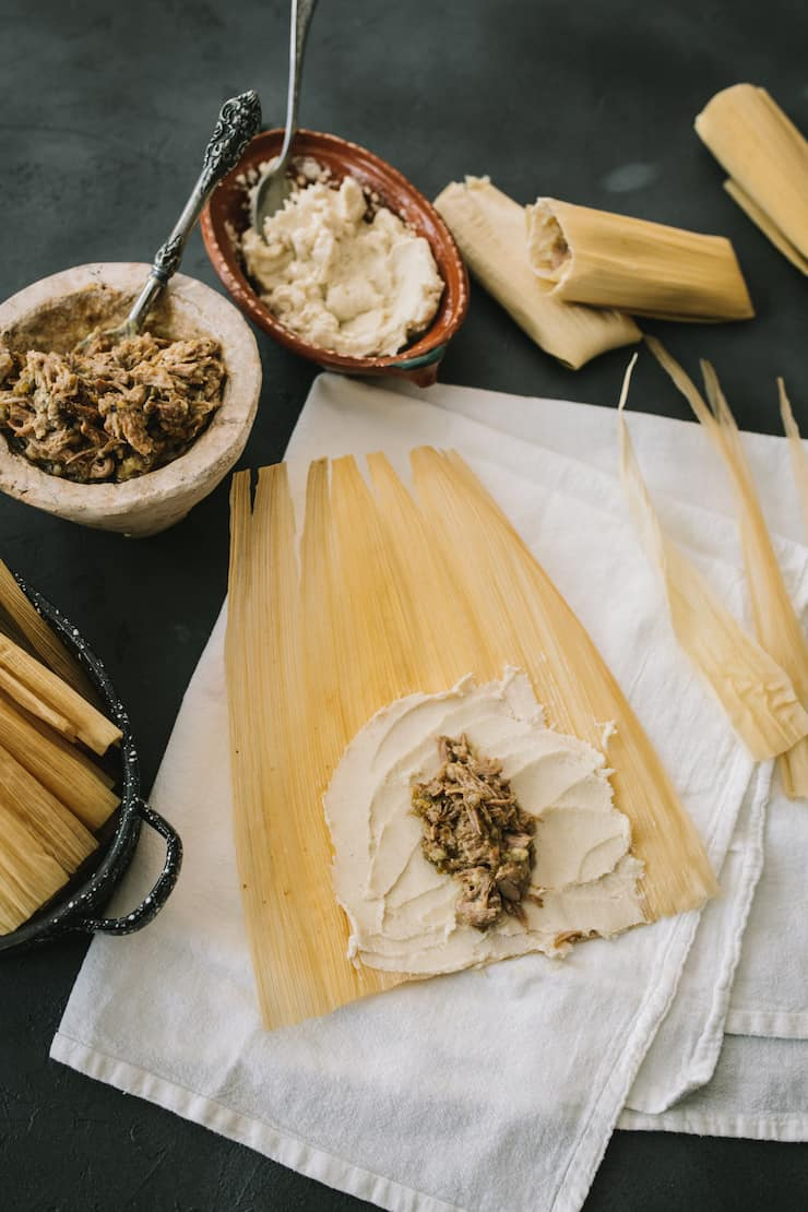 Instant Pot Pork and Roasted Green Chile spread masa to make tamales