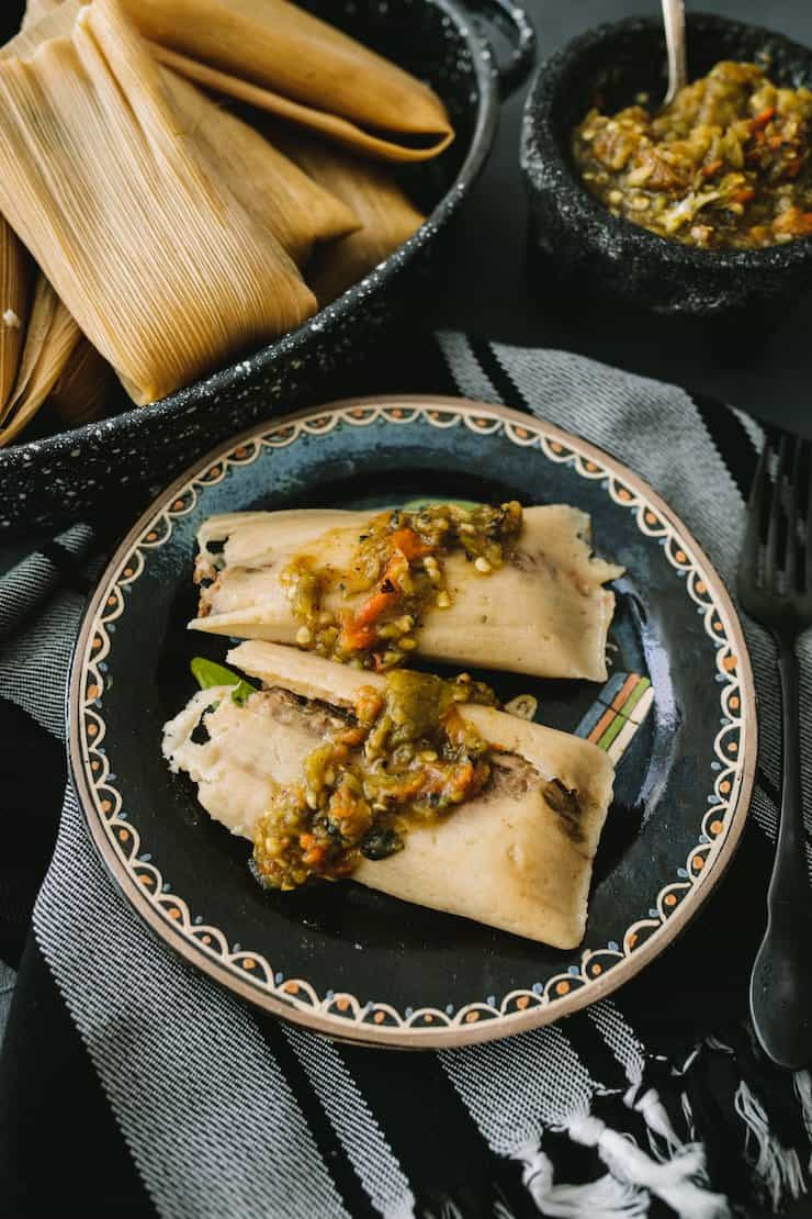 Instant Pot Pork and Roasted Green Chile Tamales plated on a black plate
