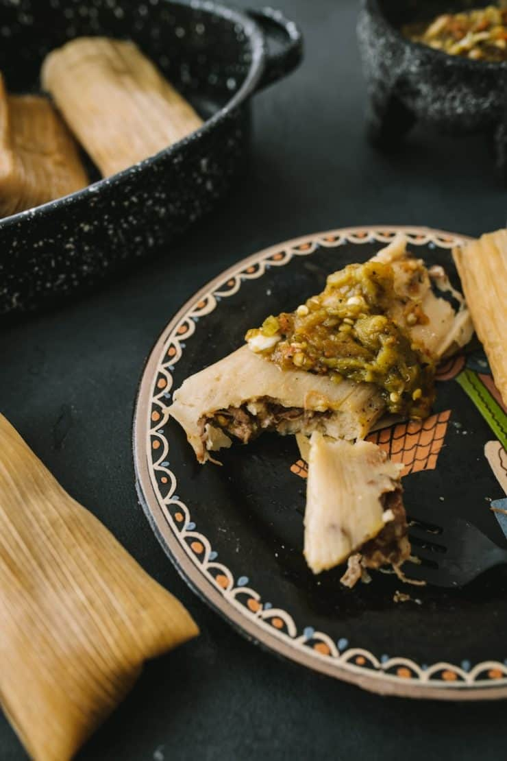 Instant Pot Pork and Roasted Green Chile Tamales with Chile on top on black plate