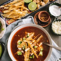 chicken tortilla soup in a white bowl next to a platter of assorted toppings
