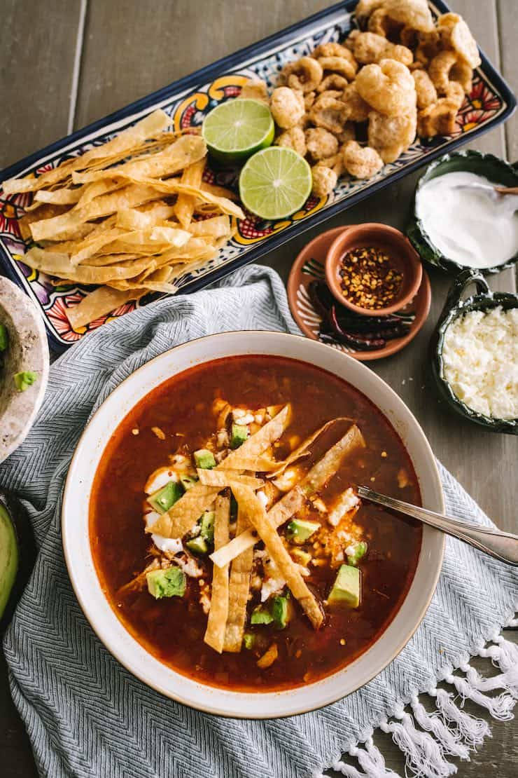 Classic chicken tortilla soup in a white bowl with an assortment of toppings on a platter nearby