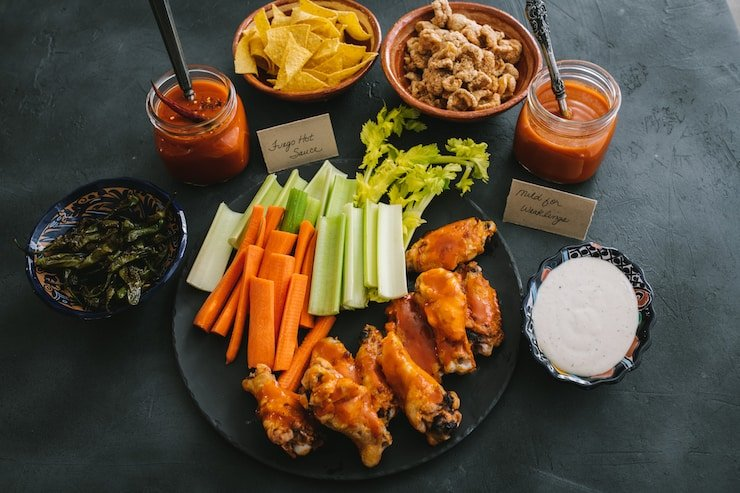 chicken wings platter with sauces celery and carrots