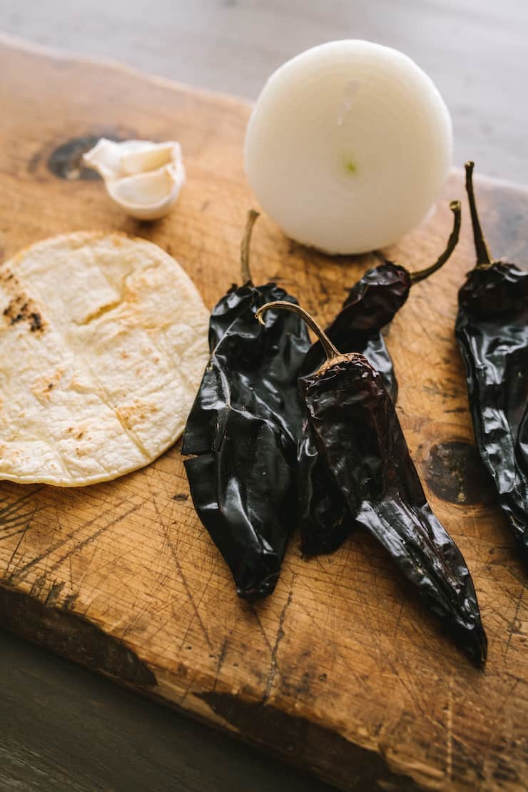 corn tortilla Chile pods onion and garlic on a wooden cutting board