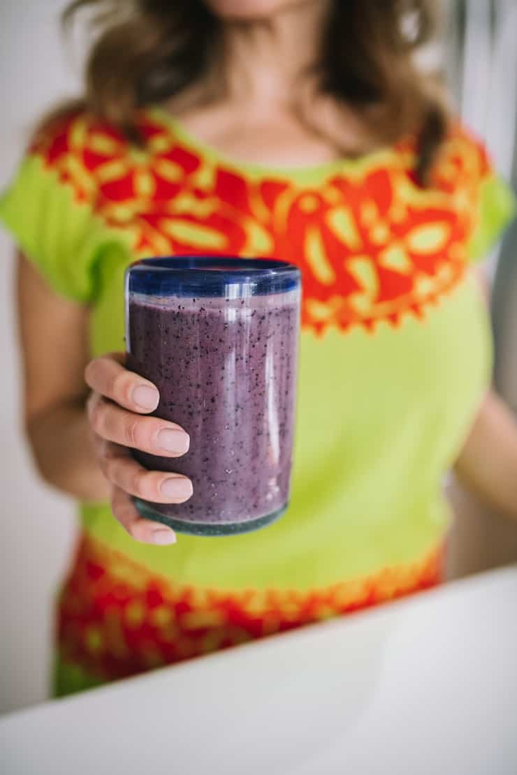 holding a glass filled with blueberry banana smoothie Smoothie Freezer Pack Recipes
