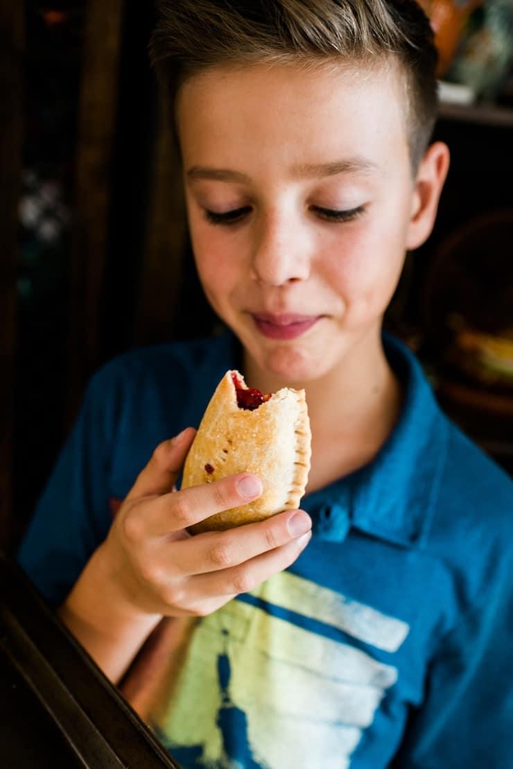 boy eating a Cherry Empanadas (Cherry Hand Pies)