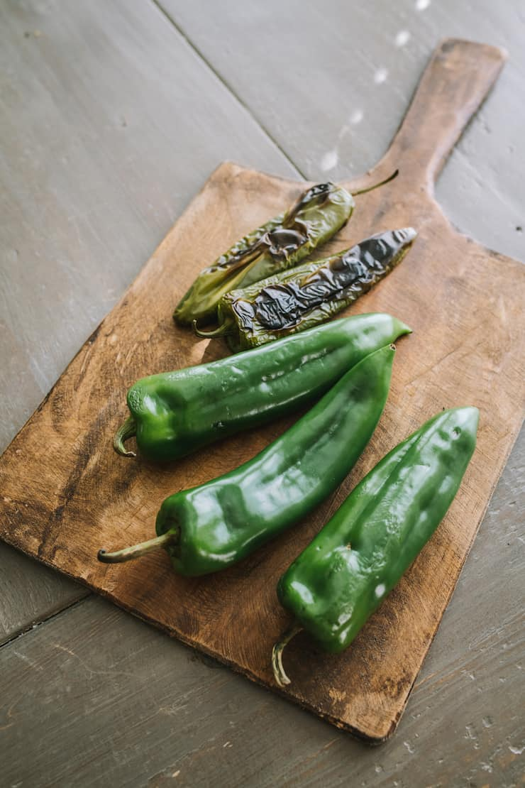 three long green chiles and two fire roasted chiles on a wooden cutting board with a handle