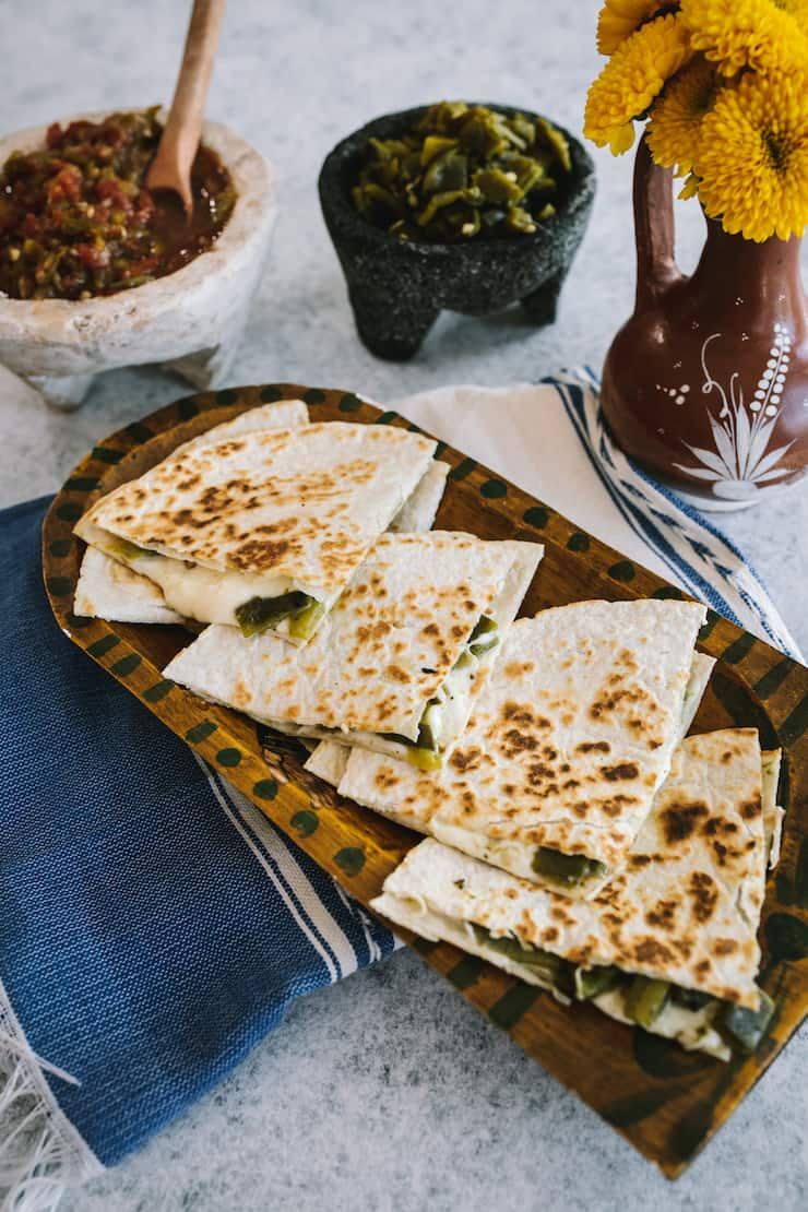 Green Chile and Cheese Quesadilla set out on a batea wooden tray