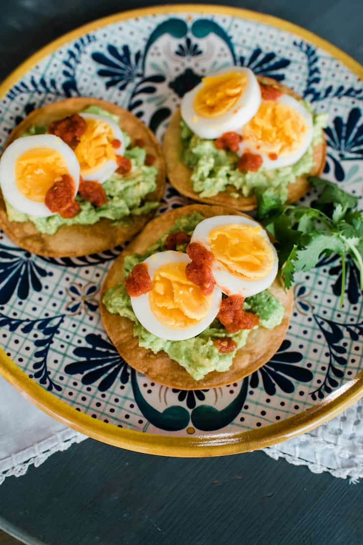 breakfast tostadas with guacamole and hard boil eggs and salsa
