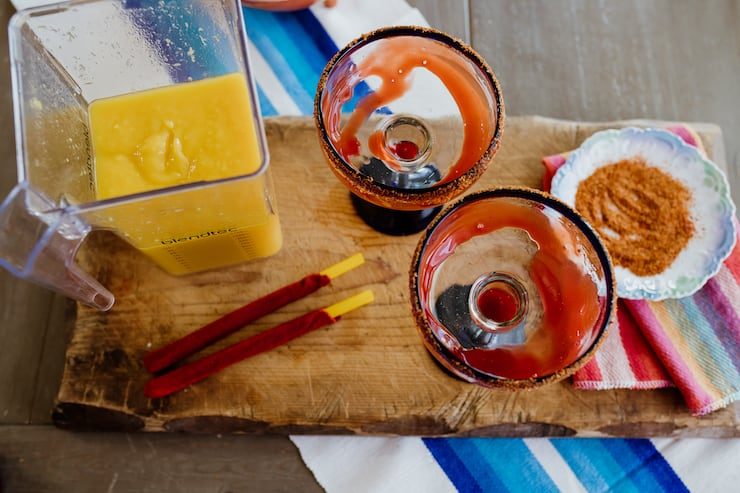 margarita glasses swirled with Chamoy Sauce and a blender of Mangonada Margaritas