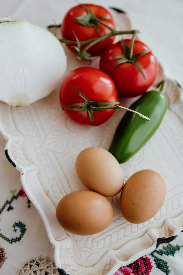 vintage white platter with 3 brown eggs jalapeño and tomatoes on the vine and white onion