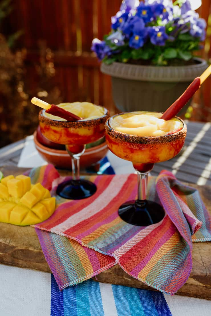two Mangonada Margaritas on a colorful striped linen