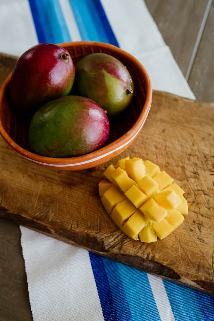three mangos in a bowl and one mango cut on cutting board