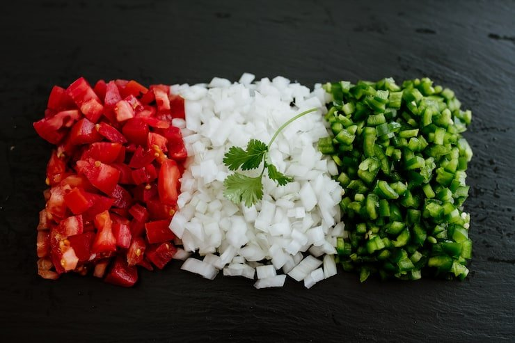 Mexican flag shaped with chopped tomatoes white onion and jalapeño