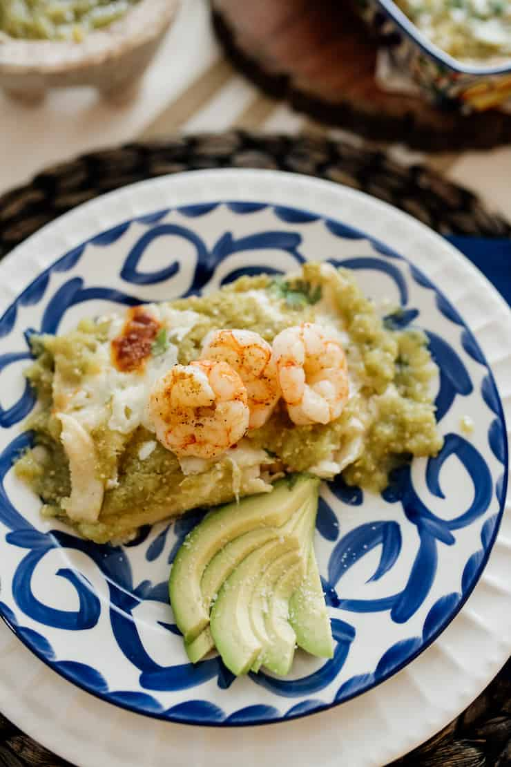 a serving shrimp enchiladas in a salsa verde with a side of slices of avocado