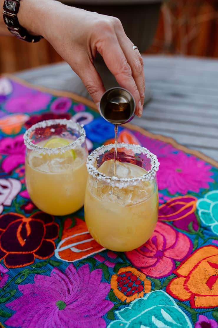 making a Cadillac margarita by pouring a shot of Grand Marnier triple sec into a margarita