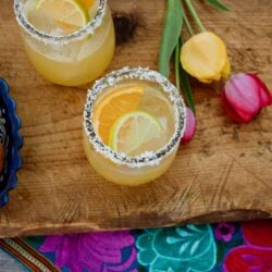 two skinny margaritas on a wooden cutting board with a colorful Mexican embroidered runner and yellow and pink tulips