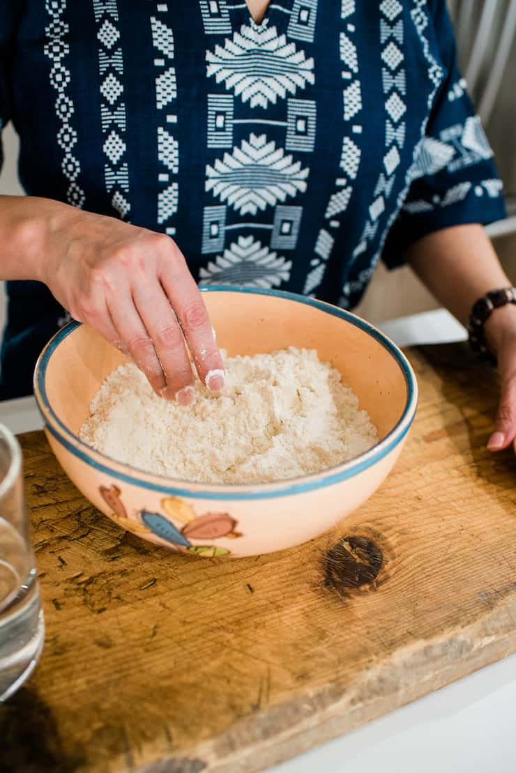 Corn flour masa harina in a Mexican vinage bowl and woman hands in bowl showing texture
