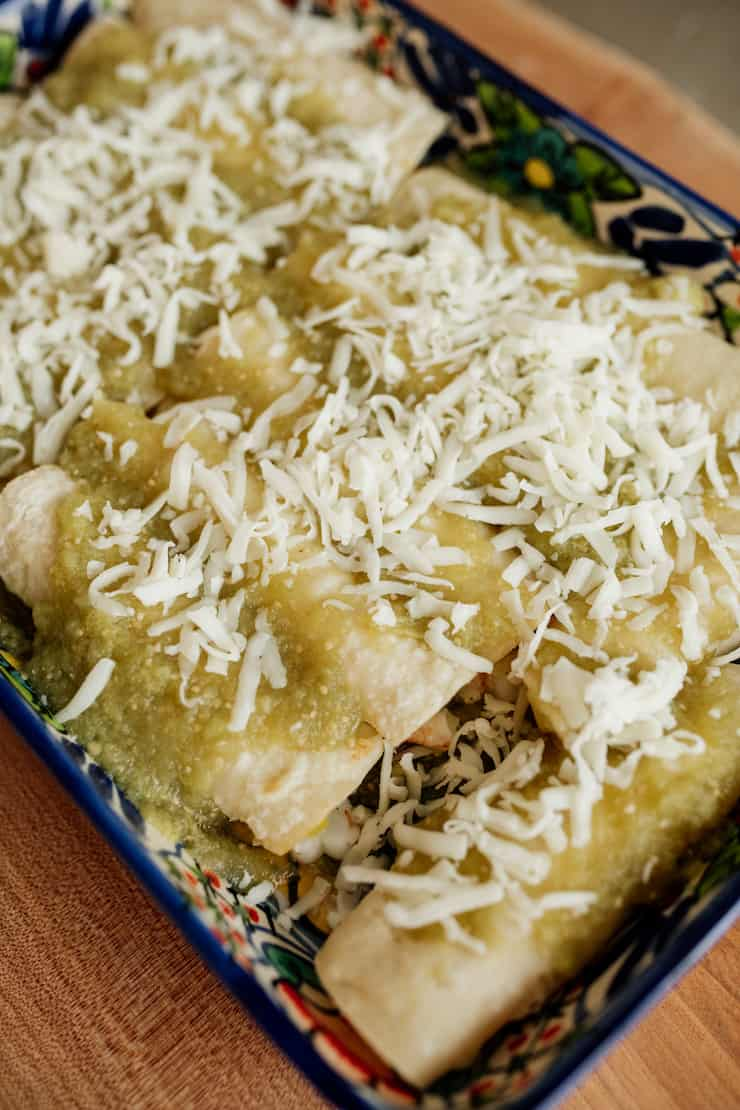 Mexican talavera baking dish with rolled enchiladas filled with shrimp and smothered with salsa verde and topped with shredded white cheese