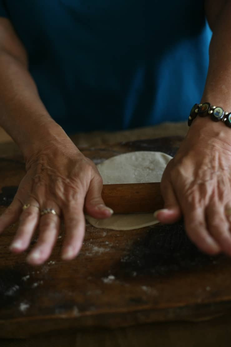 Grandma's hands rolling a flour tortilla on a wooden cutting board