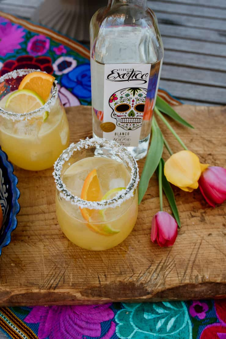 two margaritas and yellow and pink tulips bottle of Exotico tequila on a wooden board
